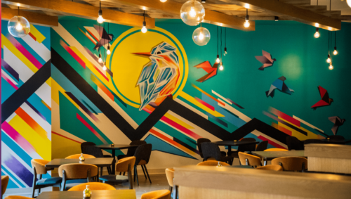 Mural of a bird in bright teal and yellow on a restaurant wall
